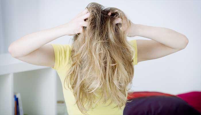 Женщина чешет голову из-за вшей